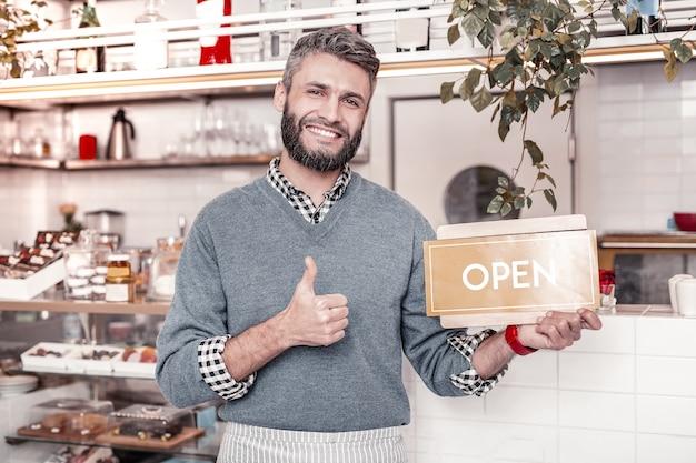 営業時間。カフェの訪問者に挨拶しながらドアの看板を持っているうれしそうな楽しい男