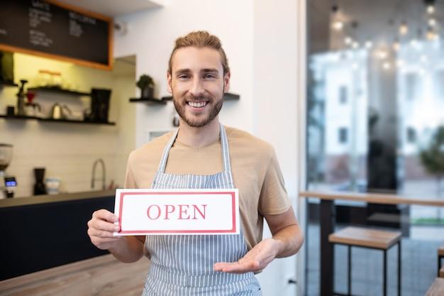 営業時間。彼のカフェに公然と立っている言葉でサインを示すを保持しているうれしそうな若い成人男性
