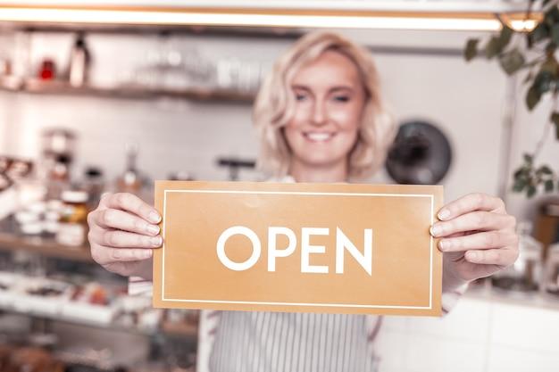 営業時間。女性の手で保持されている開いたドアの看板の選択的な焦点