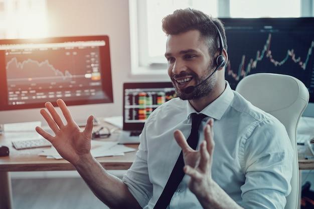 新しい機会を開く。クライアントと話し、オフィスに座って笑っているヘッドセットの青年実業家