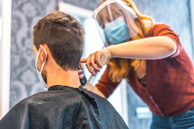 コロナウイルスの流行後の美容院のオープン、covid-19。セキュリティ対策、フェイスマスク、防護スクリーン、社会的距離。金髪白人美容院