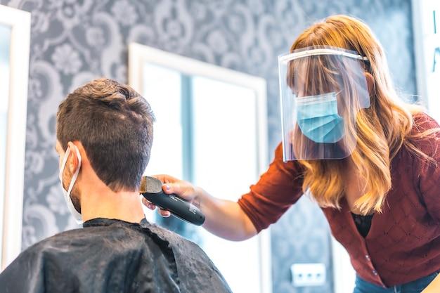 コロナウイルスの流行後の美容院のオープン、covid-19。セキュリティ対策、フェイスマスク、防護スクリーン、社会的距離。クライアントの少年にマシンで髪を切る美容師