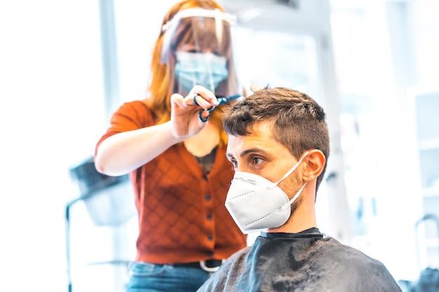 コロナウイルスの流行後の美容院のオープン、covid-19。セキュリティ対策、フェイスマスク、防護スクリーン、社会的距離。クライアントの少年にハサミで髪を切る美容師