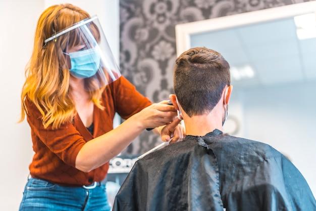 コロナウイルスの流行後の美容院のオープン、covid-19。セキュリティ対策、フェイスマスク、防護スクリーン、社会的距離。若いブルネットを扱う美容師