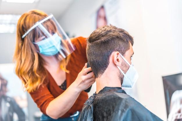 コロナウイルスの流行後の美容院のオープン、covid-19。セキュリティ対策、フェイスマスク、防護スクリーン、社会的距離。新しい通常の髪を切る美容師