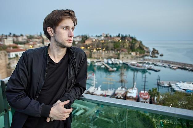 Открытие туристического сезона в анталии молодой европеец смотрит на море со смотровой площадки
