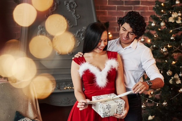 Opening the present. beautiful couple celebrating new year in the decorated room with christmas tree and fireplace behind