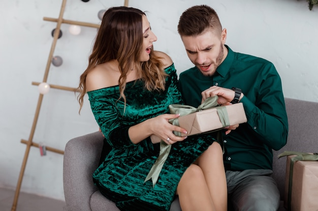 Opening  present. couple in love happy enjoy  holiday celebration. loving couple cuddle smiling while unpacking gift  tree background.what a surprise.