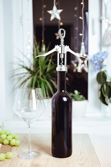 Opening of a wine bottle with corkscrew. party background, party preparation, closed bottle of red wine against background of burning garlands. christmas background