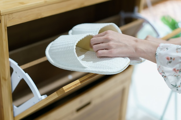 Открывая деревянный шкаф для хранения обуви, чтобы держать ее обувь