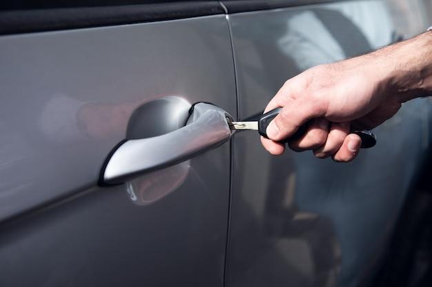 Открывает дверь машины ключом