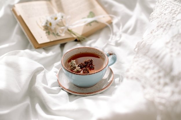 Openwork lace, cotton white blanket. book botany, mug with natural herbal tea made from mint, summer daisy flowers. morning breakfast in bed. provence retro style. clean cosiness and freshness.