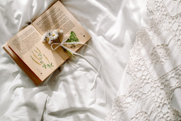 Openwork lace, cotton white blanket. book botany, mug with natural herbal tea made from mint, summer daisy flowers. morning breakfast in bed. provence and retro style. clean cosiness and freshness.