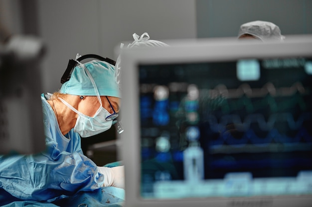 Operating room, portrait of a surgeon between computers evele and cardio, blue light. real operation. beautiful light. copy space.