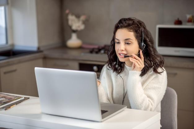 운영자. 집에서 일하는 동안 노트북에 앉아 이어폰에 연산자