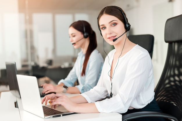 Operator in call center answers customer requests online and on the phone in the modern company office