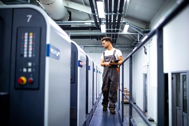 印刷工場またはプリントショップでオフセット抄紙機の印刷プロセスを制御するオペレーター