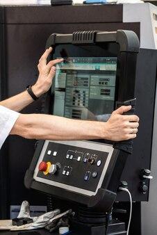 オペレーターはcncマシンの液晶画面を手渡します