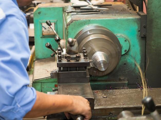 手動旋盤で金型部品を回すオペレーター