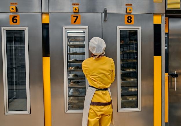 공장 오븐에 넣을 준비가 된 빵 반죽 트레이가있는 작업자. 신선한 제품으로 빵 빵집 식품 공장 생산.