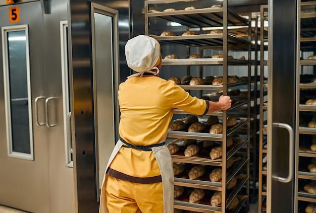 공장 오븐에 넣을 준비가 된 빵 반죽 트레이가있는 작업자.