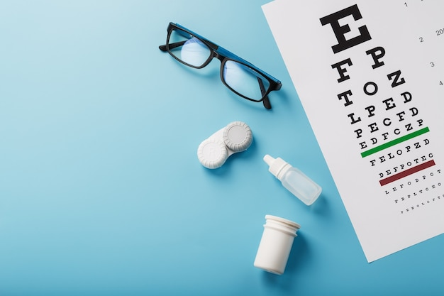 Ophthalmic accessories glasses and lenses with an eye test chart for vision correction on a blue background. treating vision problems. top view, free space