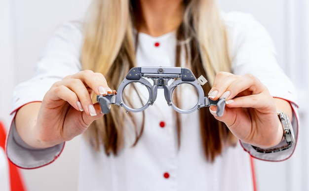 Ophthalmological trial frame and test glasses in woman's hands
