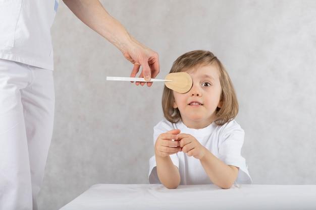 Офтальмолог неправильно закрывает мальчику глаза наглазником. серый фон
