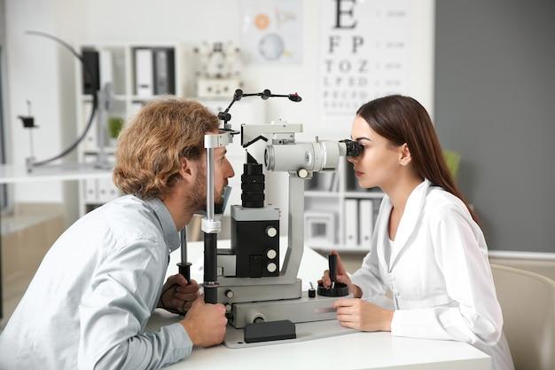 クリニックで若い男性を診察する眼科医