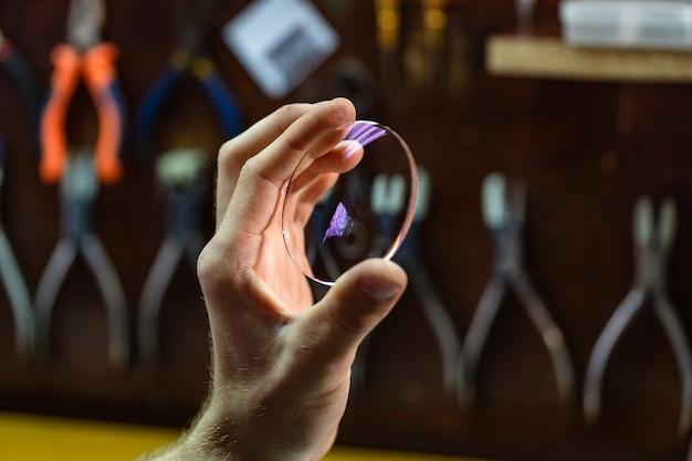 眼科医の手をクローズアップし、眼鏡用のガラスレンズを見せます