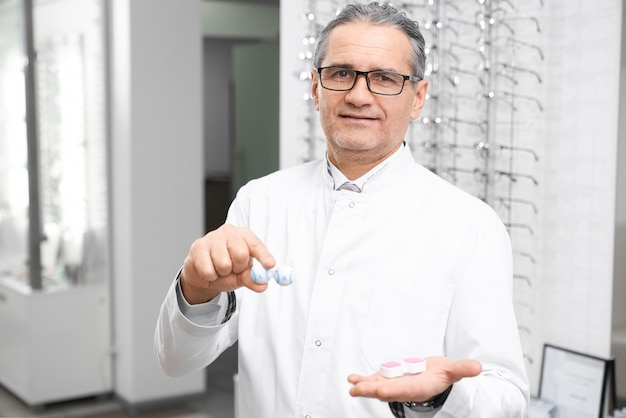 Ophthalmologist holding container for lenses in medical room