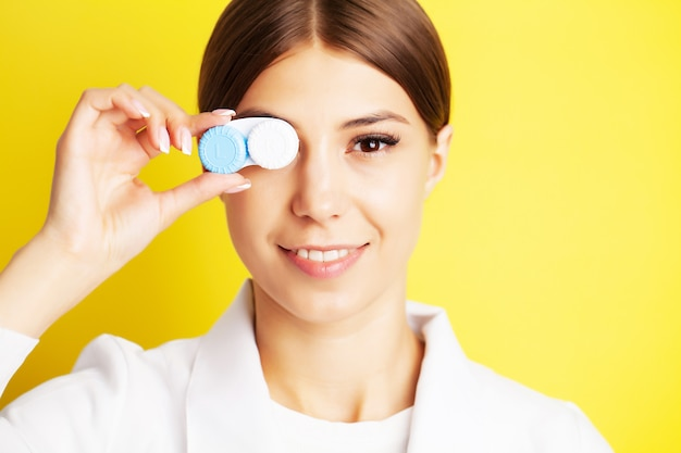 The ophthalmologist holds a container with contact lenses near the eyes