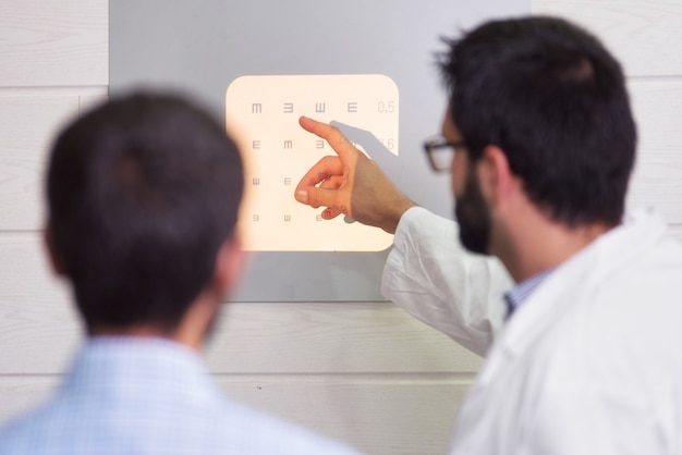 Ophthalmologist pointing at letters while patient is reading the eye chart.
