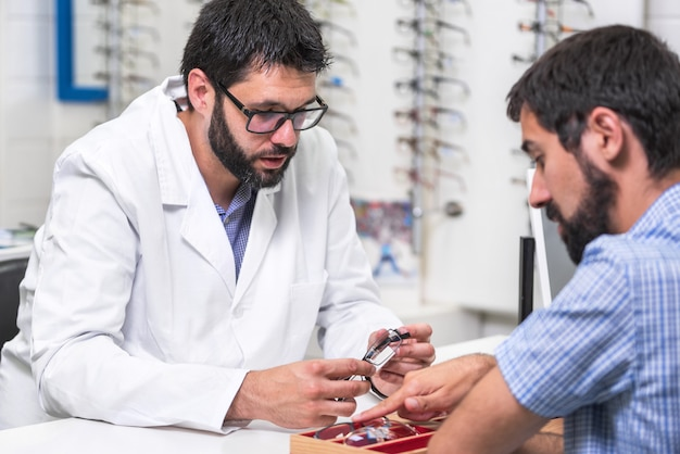 Ophthalmologist showing a tray with different glasses to a customer.