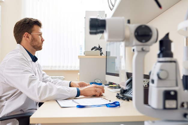 Ophthalmologist working with computer in office