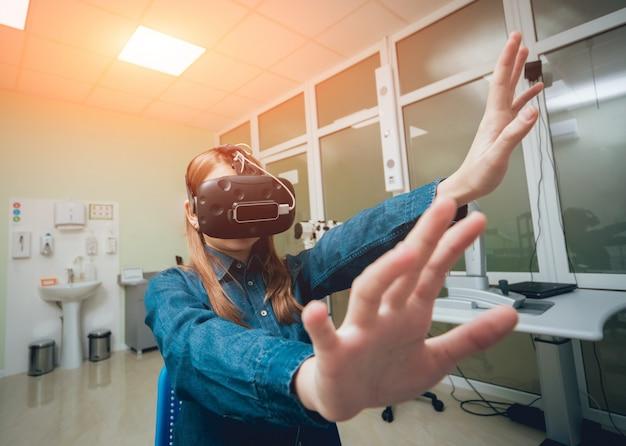 Врач-офтальмолог проверяет зрение девушки с помощью очков виртуальной реальности.