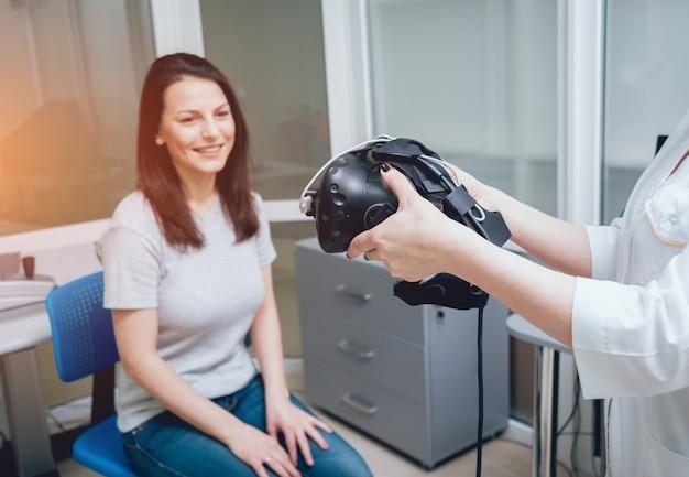 眼科医は、バーチャルリアリティゴーグルを使用して少女の視力をチェックします。