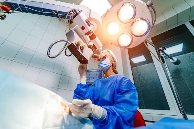 Офтальмологическая операция. руки хирурга в перчатках, выполняющих лазерную коррекцию зрения с микроскопом. концепция современной клиники.