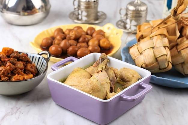 Opor ayam (индонезийский желтый куриный карри) для меню lebaran, подается с ketupat, sambal goreng ati kentang и semur telur. популярное блюдо для ид аль фитр