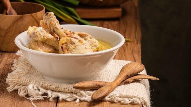 Opor ayam подают на деревянном столе. опор - это традиционное индонезийское блюдо из курицы, приготовленное с кокосово-молочным соусом.