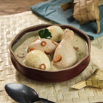 Opor ayam telur, курица и вареное яйцо, приготовленные на кокосовом молоке из индонезии, подаются с лонтонгом или кетупатом и самбалом. популярное блюдо на лебаран или курбан-байрам