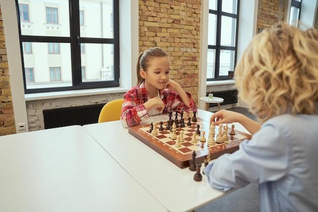 보드에 반대하는 아름다운 소녀는 친구와 체스를 하는 동안 그녀의 움직임을 계획합니다