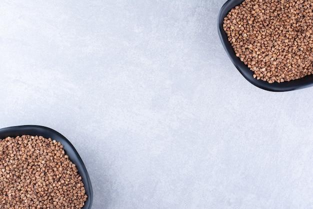 대리석 표면에 반대로 배열된 생 메밀 그릇