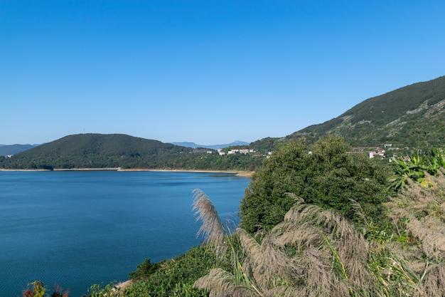Напротив озера гора, небо голубое, а вода в озере голубая