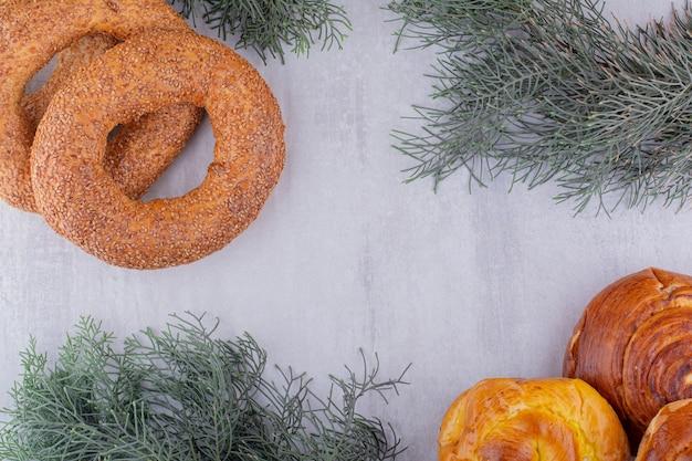 반대 방향으로 정렬 된 베이글과 흰색 바탕에 달콤한 빵. 무료 사진