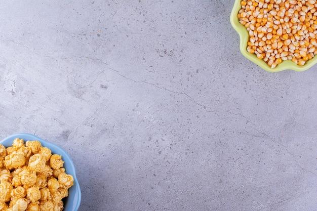 옥수수 커널과 대리석 배경에 캐러 미 맛이 나는 팝콘 더미로 채워진 반대 방향으로 정렬 된 그릇. 고품질 사진
