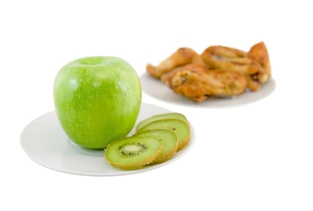 反対-健康的な食事のリンゴとキウイ、または背景の不健康な食事-ローストチケン。孤立