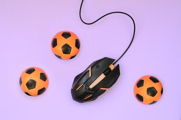 Оптическая игровая мышь и маленькие оранжевые футбольные мячи