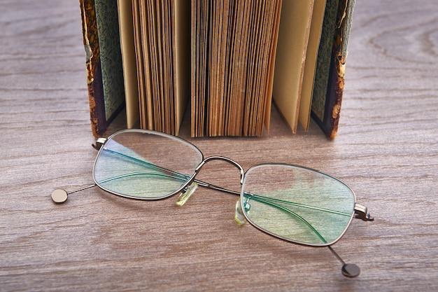 Оптические очки лежат на деревянном столе рядом со старинной книгой