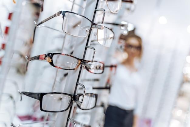 光学ショップ。眼鏡技師は眼鏡を提案します。バックグラウンドで多くの眼鏡をかけて立っている女性。